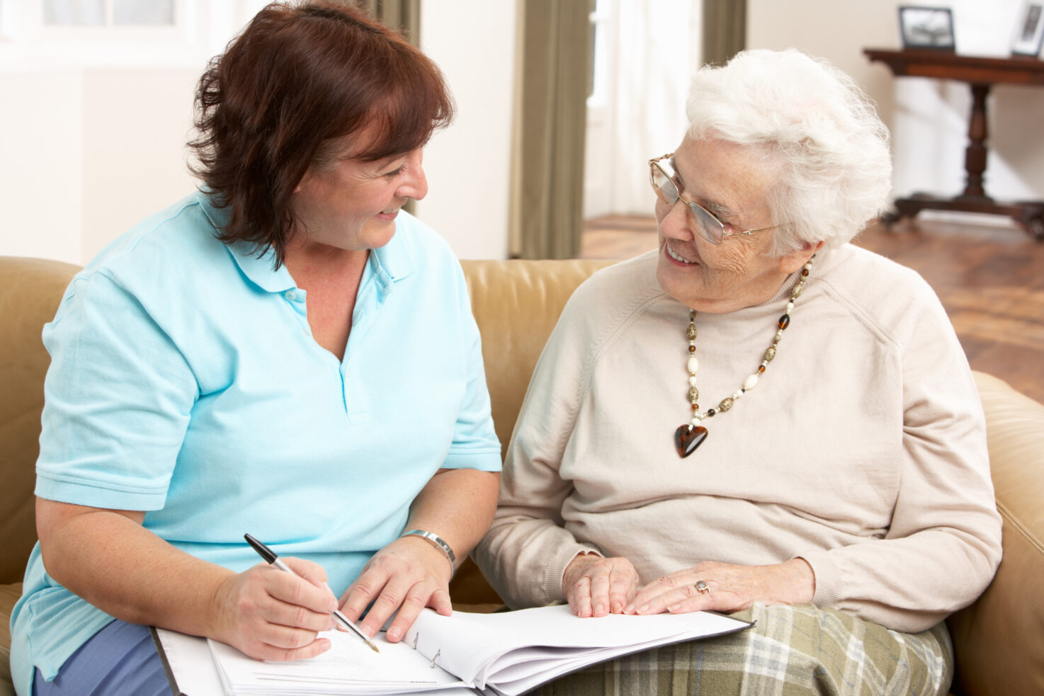 Senior Woman In Discussion With Caregiver At Home